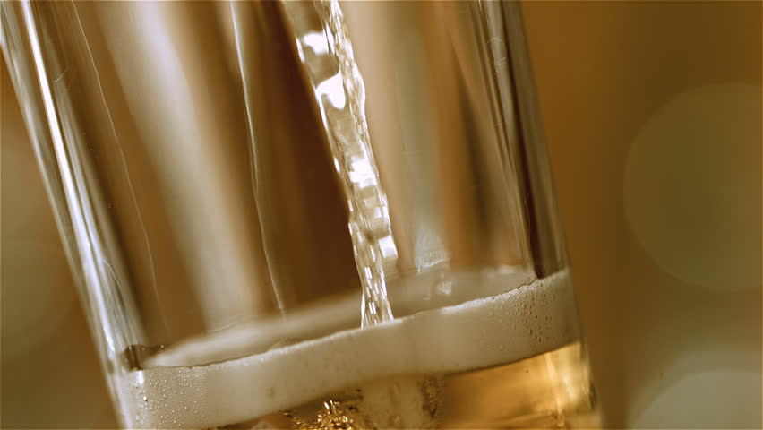 Beer is pouring into the angled glass. - HD stock footage clip