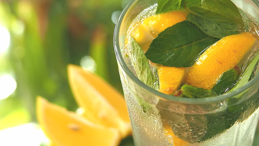 a glass with lemon, mint and ice cubes