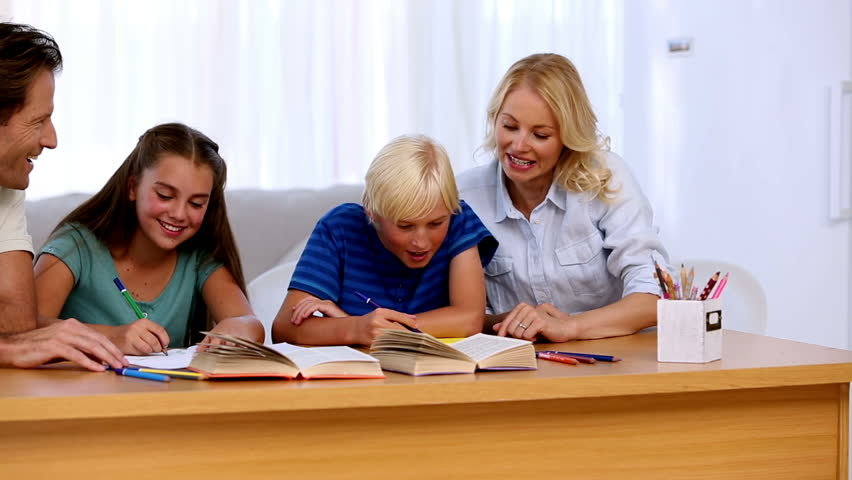 Parents helping their children with their homework at a desk | Shutterstock HD Video #3870533