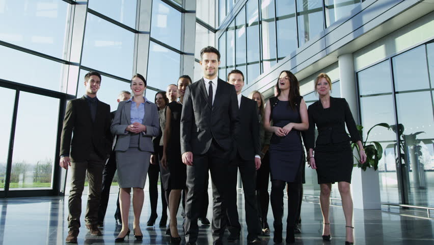 Portrait of a diverse group of business people, walking through  a light and modern glass fronted office building on a bright day. In slow motion.