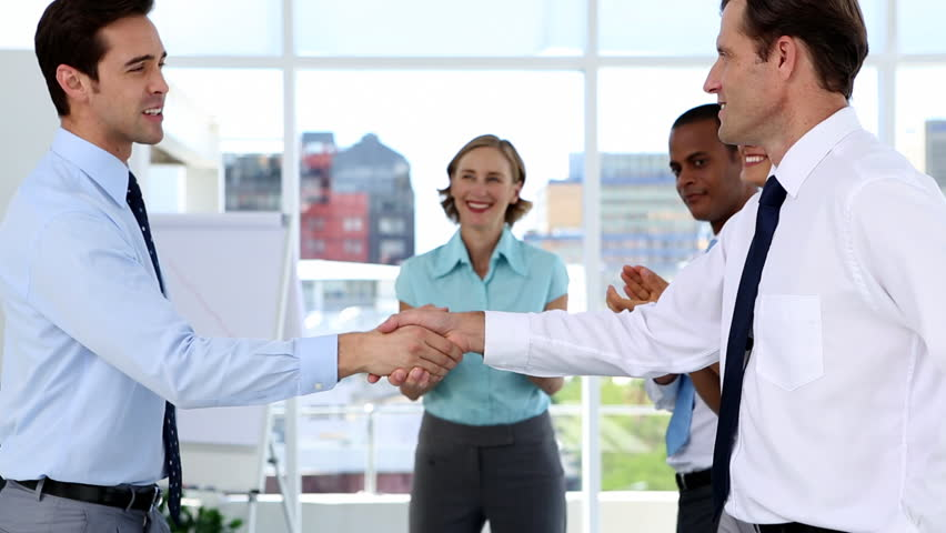 Businessmen shake hands while other business people applauding in a bright office #3872603