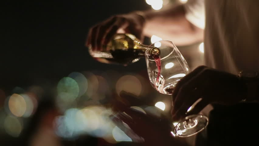 Man pouring wine into glasses at a party | Shutterstock HD Video #3892664