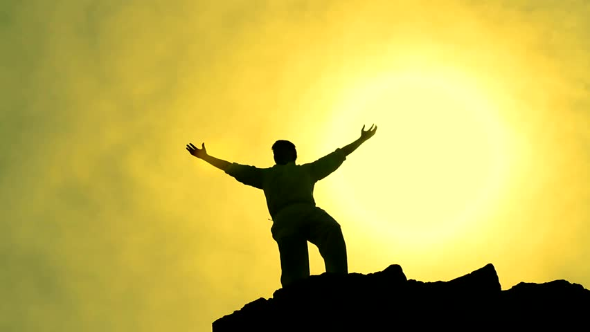Success Pose by Man on Top of Hill Lifting Hands toward Sun Color Background silhouette
