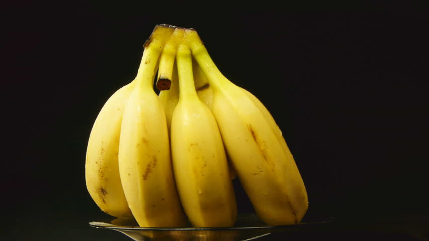 Bunch of bananas rotating on black background - HD stock video clip