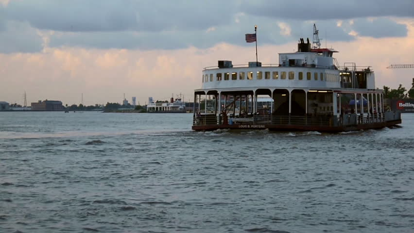 New Orleans, Louisiana -  June, 2011 - Wide shot of a ferry sailing away from New Orleans and towards Algiers at dusk.