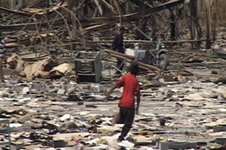 BAGHDAD, IRAQ - JULY 26, 2003: Boy runs through rubble and debris, then slows to a walk.
