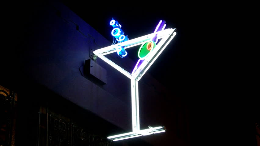 Close up, low angle shot of a neon martini glass sign on a tavern at night. This shot really captures the vibrant colors of the neon.