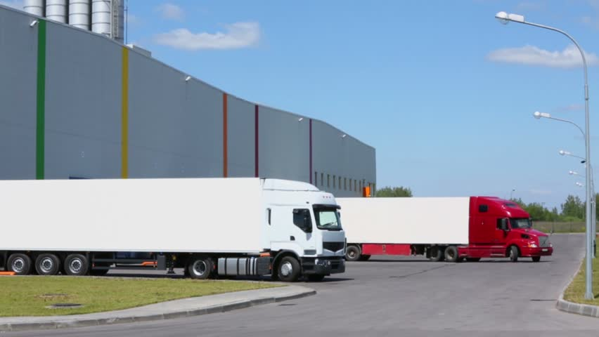 Truck rides from warehouse of factory at sunny summer day