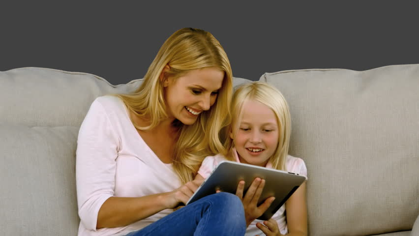 Mother and her daughter using digital tablet on sofa in slow motion on grey screen - HD stock footage clip