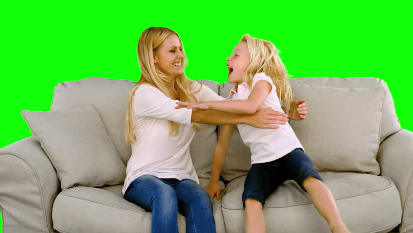 Daughter jumping in the arms of her mother on green screen in slow motion - HD stock footage clip
