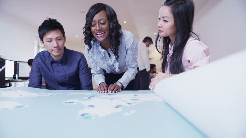 A multi-ethnic business team are working in a light and modern open plan office. They are looking at a map of the world and discussing possibilities for future business ventures. In slow motion.