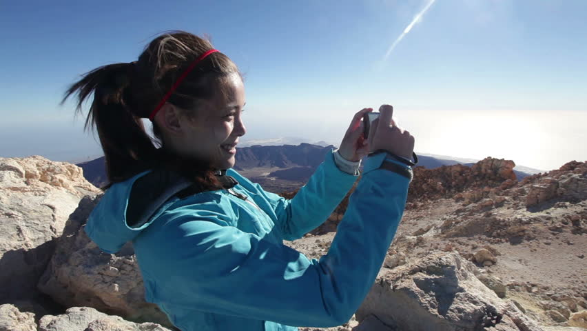 Hiker woman photographing taking pictures on mountain summit top of the volcano, Teide, Tenerife of Canary Islands, Spain. Happy female hiking and taking photos. Mixed race Asian Caucasian girl hiker.