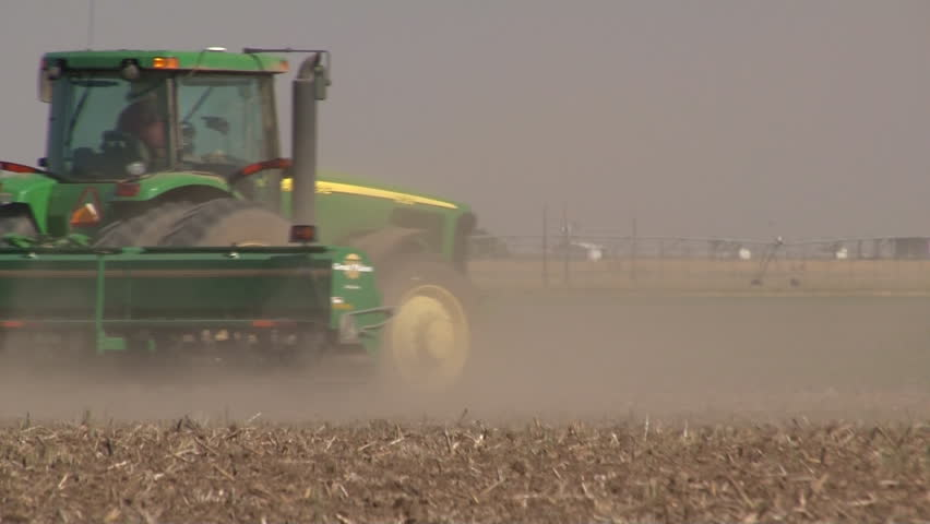 Wind blows dust behind farm tractor during West Texas drought. - HD stock video clip