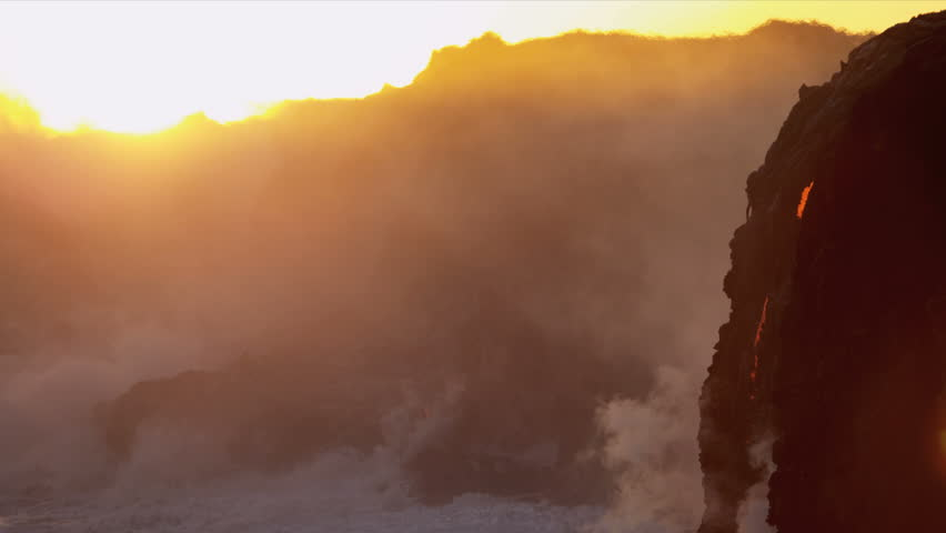 Red hot lava falling over barren landscape Kilauea Big Island into ocean sunset causing rising steam shot on RED EPIC | Shutterstock HD Video #4237697