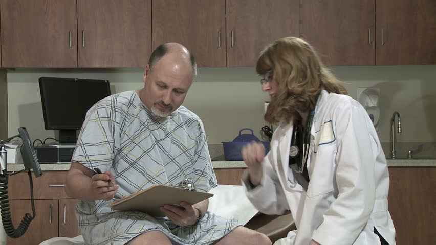 Dolly from left to reveal mature male patient visiting doctor and filling in forms on a clipboard. - HD stock footage clip