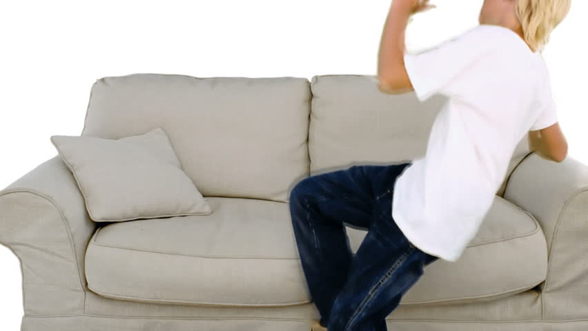 Young Boy Jumping On The Sofa On Green Screen In Slow
