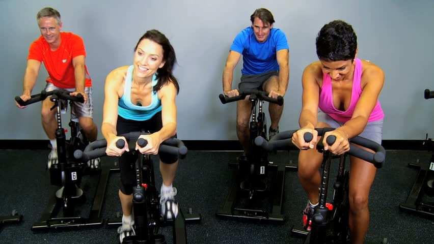 Male female gym members keeping fit riding modern exercise bikes - HD stock footage clip