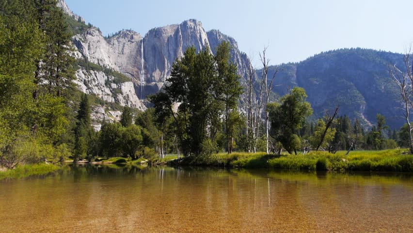 the spectacular yosemite falls and the calm waters of the merced river in  yosemite national park - HD stock video clip