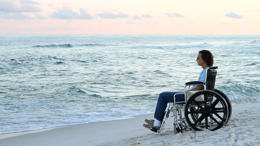 Lonely disabled woman sits and thinks in her wheelchair at the water's edge watching the ocean waves. - HD stock footage clip