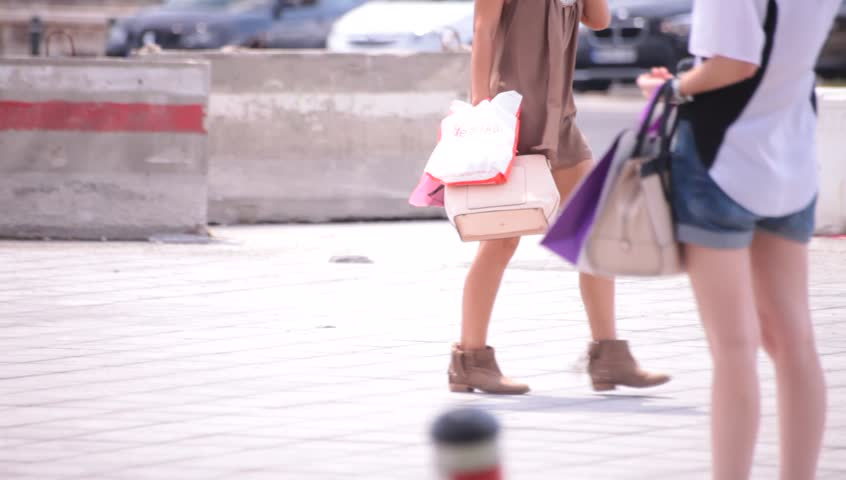 Hot sexy legs of young adult women walking down the street. Hot weather illustrative shot.