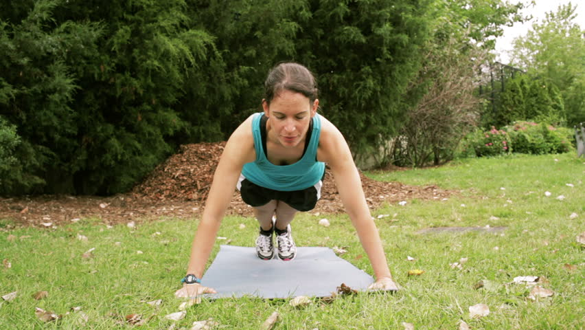front view of beautiful slim fit athletic woman outside doing push ups exercising and training outside outdoor in the park on a yoga mat