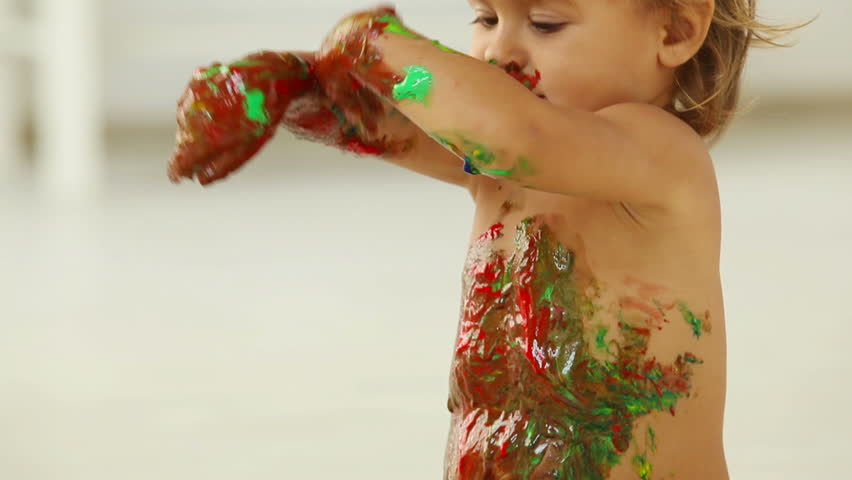 Child covered in paint moving, dancing and having fun - HD stock footage clip