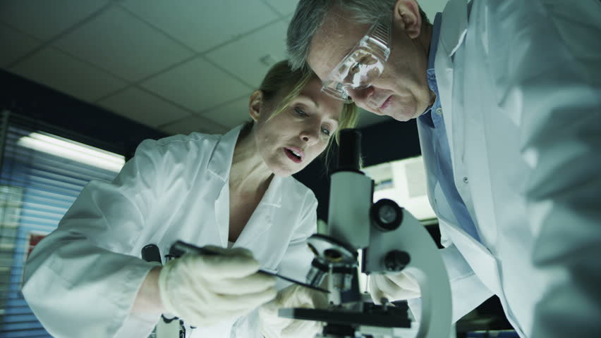 Mature male and female medical researchers working together in a dark laboratory, looking through microscopes and discussing their work.