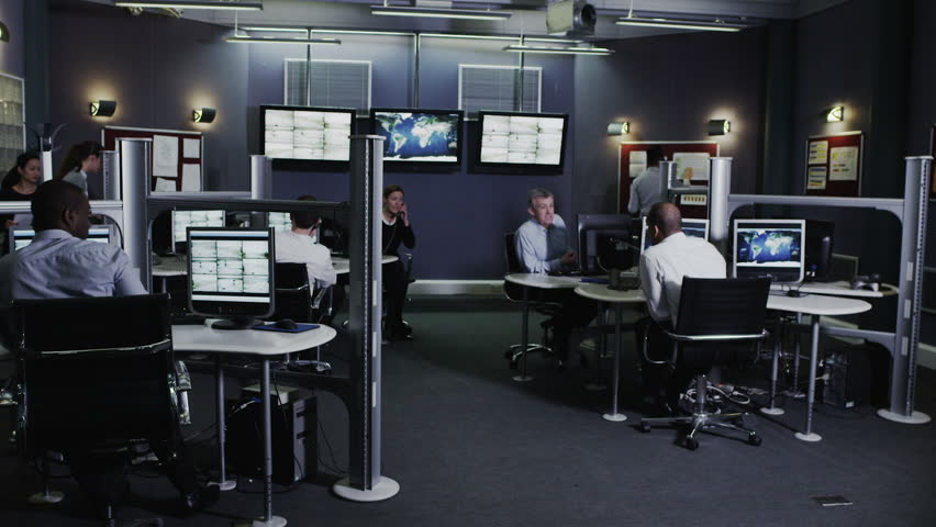 Team of security personnel watching the screens in a system control center. This could be a weather station or airport traffic control room. It could be a police or government surveillance facility.