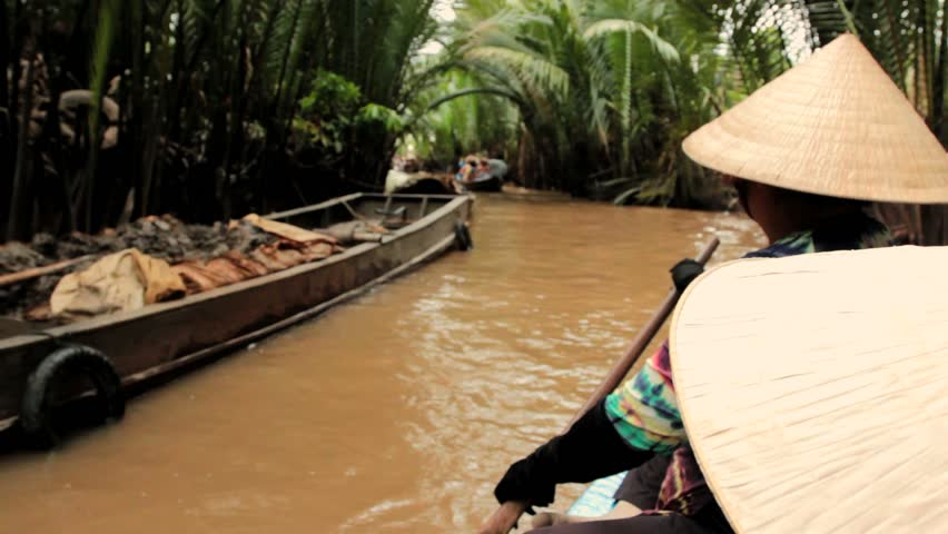 Vietnamese woman rowing a boat on a canal in Mekong delta, Vietnam
