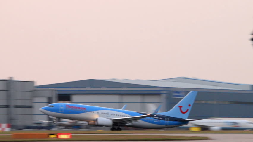 MANCHESTER, LANCASHIRE/ENGLAND - JULY 17: Thomson Boeing 737 plane takes off at sunset on July 17, 2013 in Manchester. Thomson Airways is the world's largest charter airline.