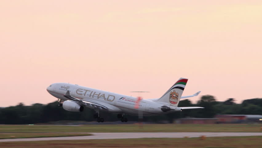 MANCHESTER, LANCASHIRE/ENGLAND - JULY 17: Etihad Airways Airbus A330 plane takes off at sunset on July 17, 2013 in Manchester. Etihad is the carrier for United Arab Emirates, founded in 2003.