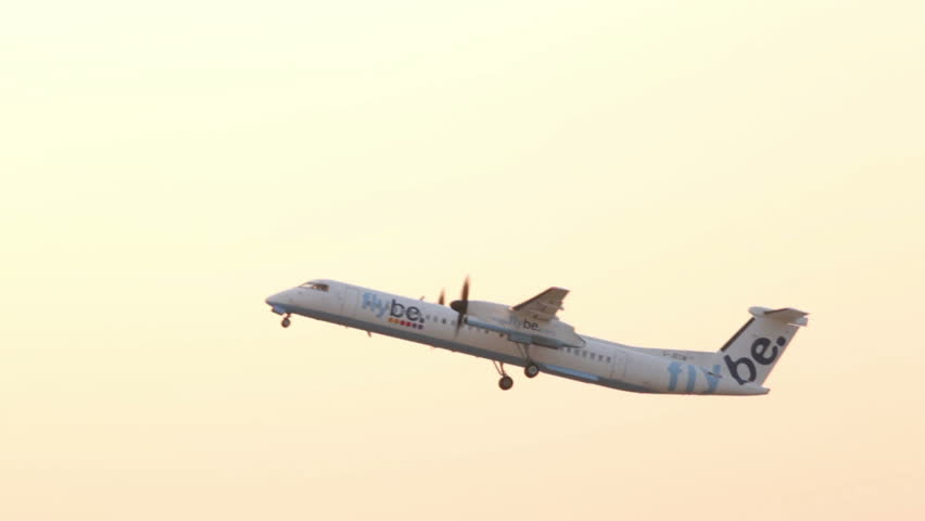 MANCHESTER, LANCASHIRE/ENGLAND - JULY 17: Flybe De Havilland Dash 8 plane takes off at sunset on July 17, 2013 in Manchester. Flybe is a British low cost regional airline based in Exeter, Devon.