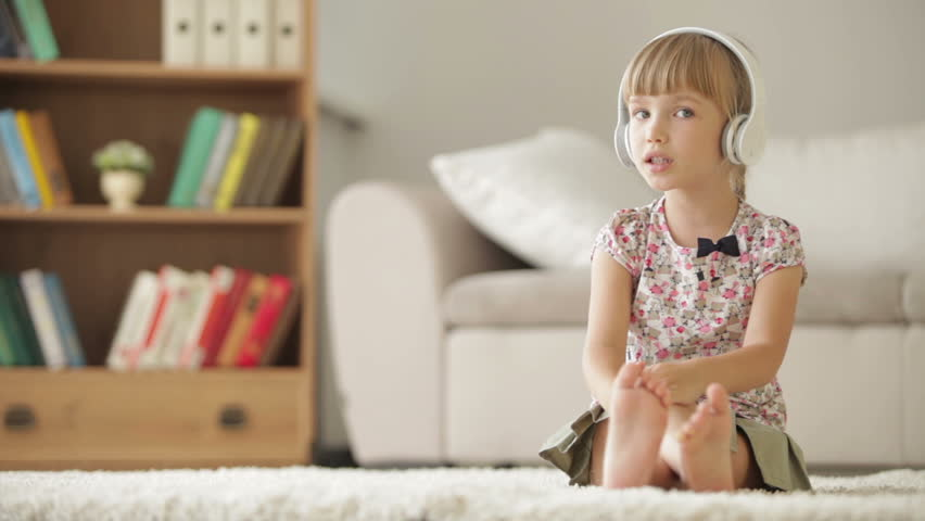 Funny little girl in headphones sitting on carpet in living room singing, moving