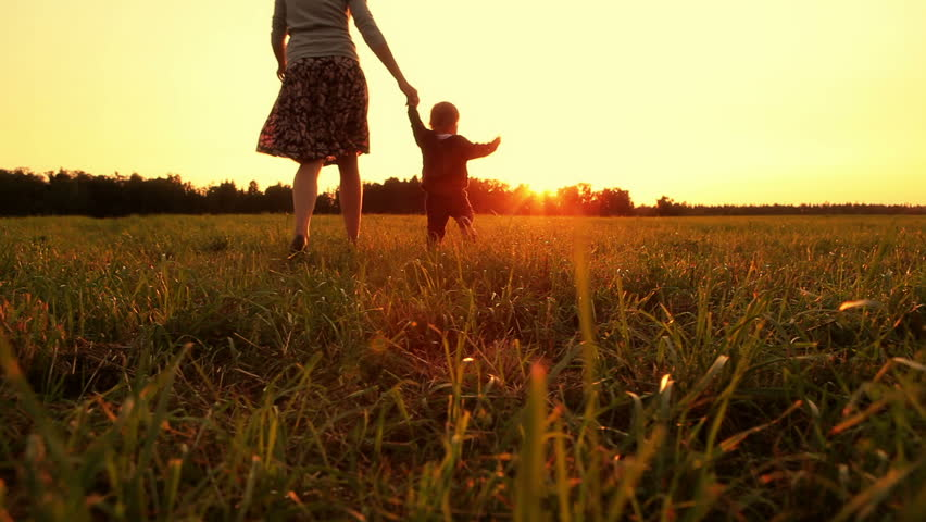 Mother and baby are running across the field at sunset (dolly shot) | Shutterstock HD Video #4384109