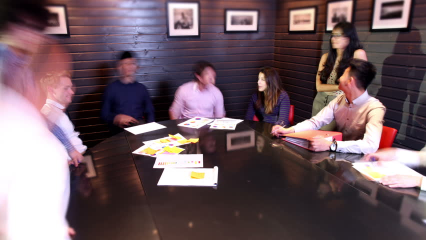 Time lapse shot of a young and attractive business team of mixed ethnicity, holding a brainstorming meeting around a large modern conference table. - HD stock footage clip