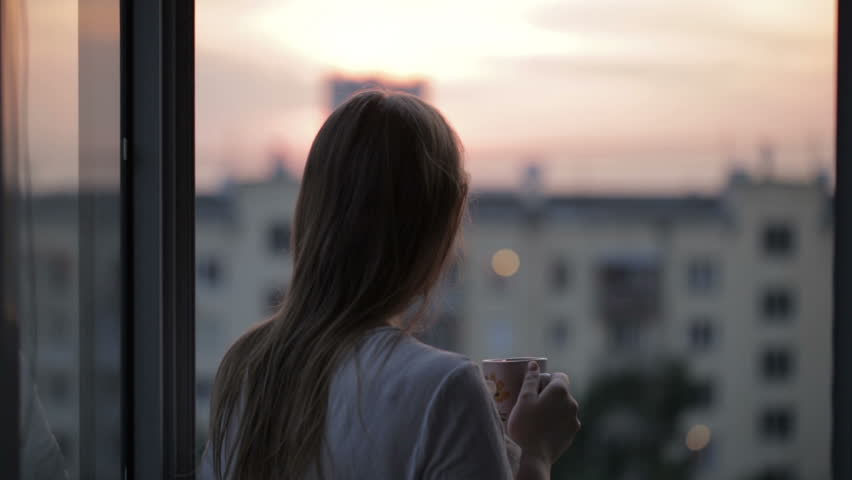Young girl on the balcony watching the sunset and drinking tea. Middle shot #4417805