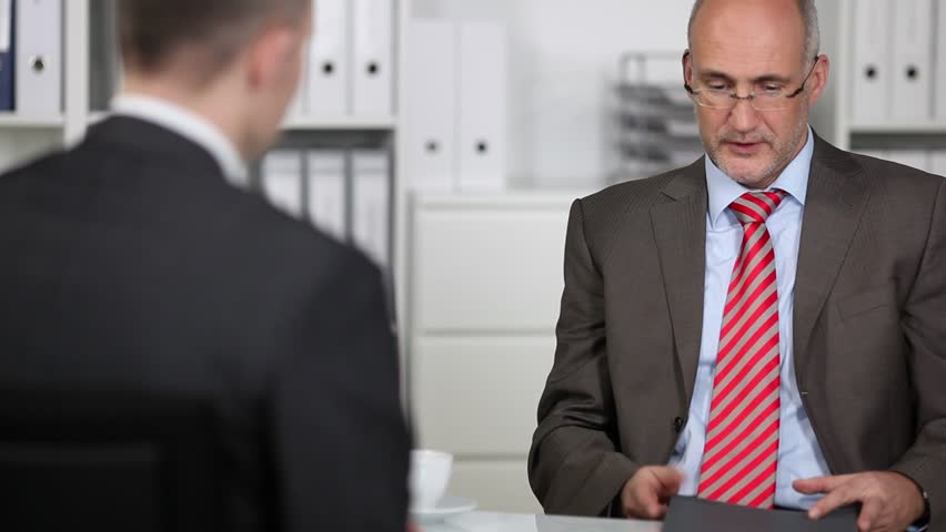 Good looking middle-aged male personnel officer in a job interview reading the CV and testimonials of the business applicant, over the shoulder view