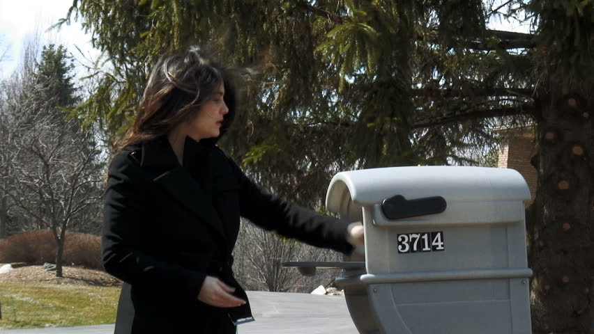 Young woman goes to get the mail.