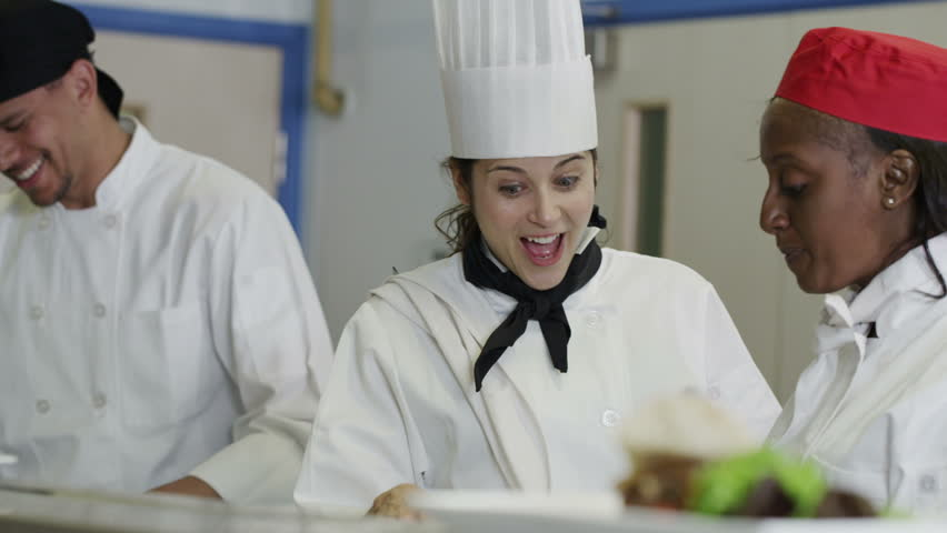 Mixed ethnicity team of professional chefs preparing and cooking food in a commercial kitchen. The head chef tastes a dish and gives her approval. In slow motion
