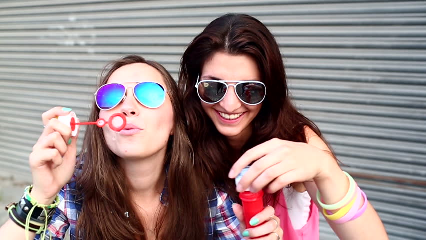 Cheerful hipster girls with sunglasses having fun making bubbles #4435724