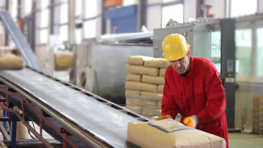 Worker controls sacks of sugar on the conveyor belt in a sugar factory - HD stock video clip
