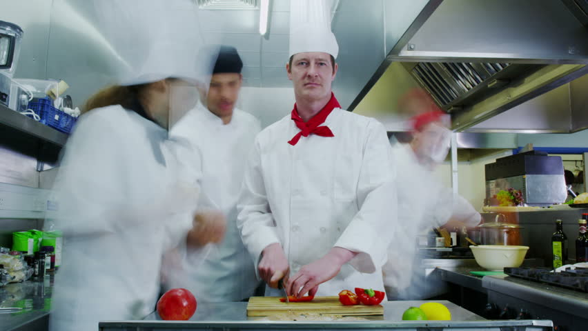 Time lapse clip of a busy team of chefs, working hard and preparing food in a commercial or restaurant kitchen. One male chef stands frozen in time while his colleagues bustle around him. - HD stock video clip