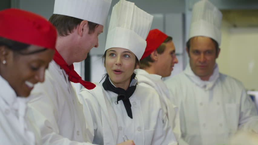 Happy mixed ethnicity team of professional chefs preparing and cooking food in a commercial kitchen.