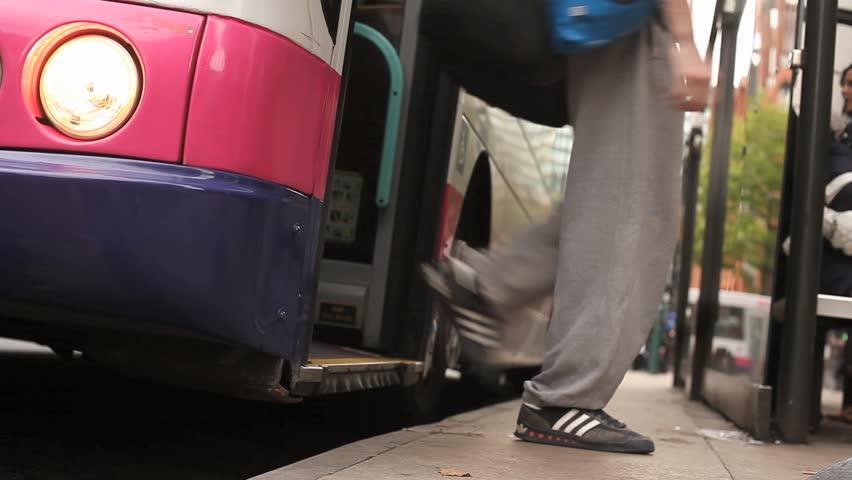 A bus drops off passengers then sets off. Handheld camera