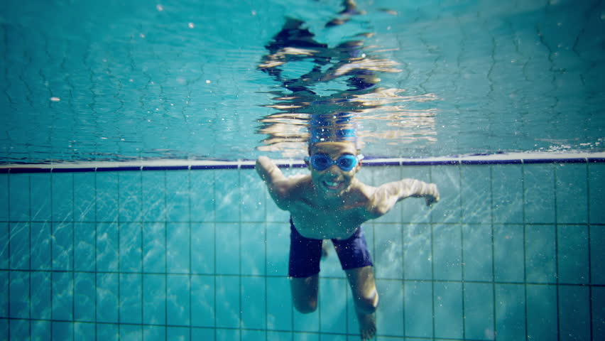 Happy cute little boy underwater is waving and smiling at the camera. - HD stock footage clip