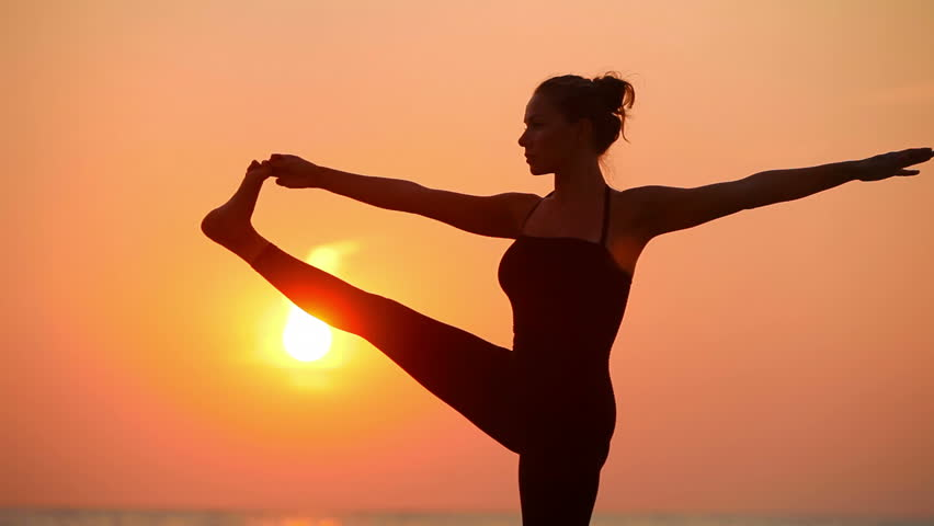a young woman with a slender figure is engaged in gymnastics at sea at sunrise silhouette