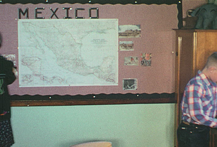 UNITED STATES - 1950s: students work at bulletin board labeled MEXICO. few boys play with paper mache animal display. teacher puts it on shelf, boy picks it up as she walks away, shows it to others.