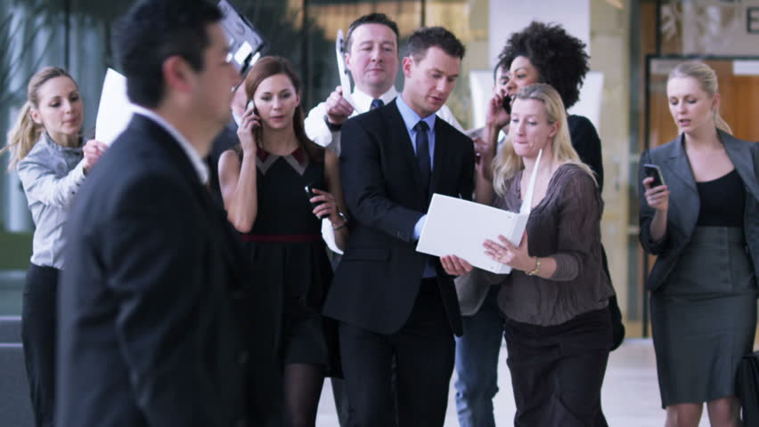 Successful Businessman with his entourage of staff vying for his attention. A large group of walking business people in offices rush to make timely decisions.