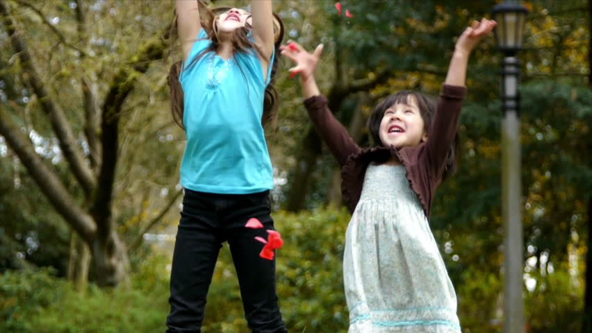 Adorable Asian Sisters Throwing Flower Petals In The Park