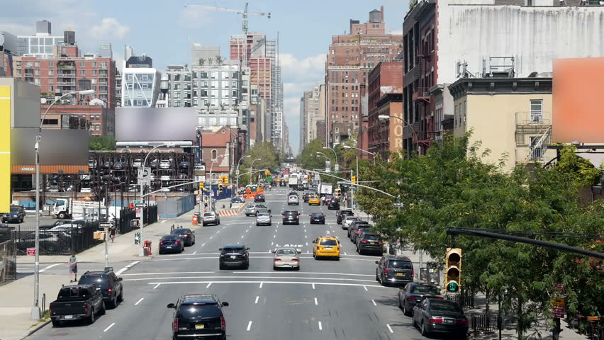 Looking down a street in Manhattan.  The billboard contents removed for general